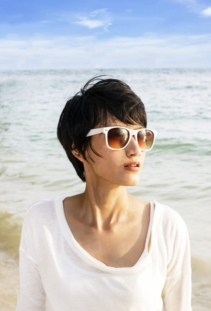 Short hair Asian woman on the beach with sunglasses and short hair cut